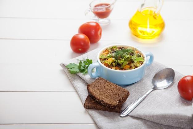 Soupe aux haricots et aux olives aux herbes dans un bol en céramique, tomates, huile d'olive et pain sur une table en bois blanc.