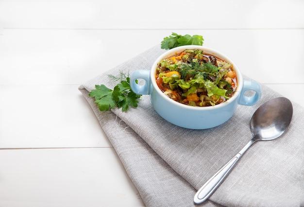 Soupe aux haricots dans un bol bleu en céramique avec tomates, olives et persil, une cuillère sur une table en bois blanc.