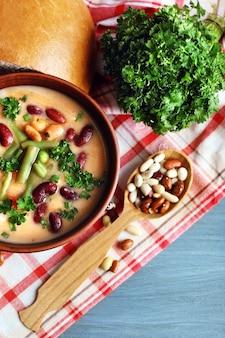 Soupe aux haricots dans un bol avec du pain frais sur une serviette, sur fond de table en bois