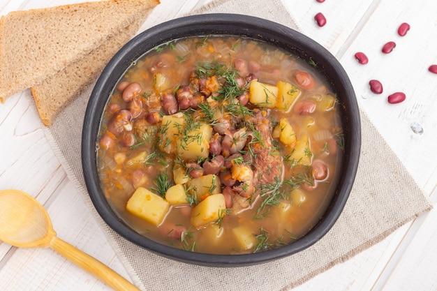 Soupe aux haricots rouges avec de la viande dans un bol en argile noire