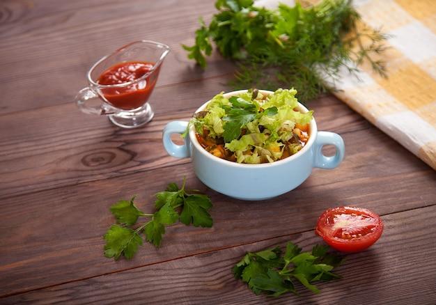 Soupe aux haricots, tomates, haricots, persil sur une table en bois.