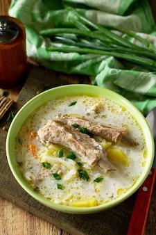 Soupe aux légumes avec crème sure au chou et côtes levées sur une table en bois de cuisine