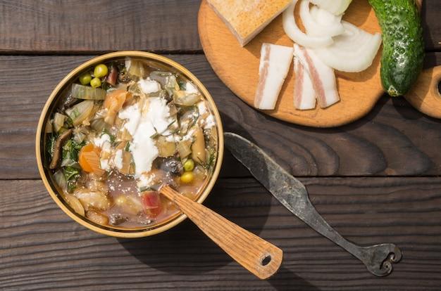 Soupe aux légumes et crème sure dans une assiette creuse à la surface des planches sombres. vue de dessus.