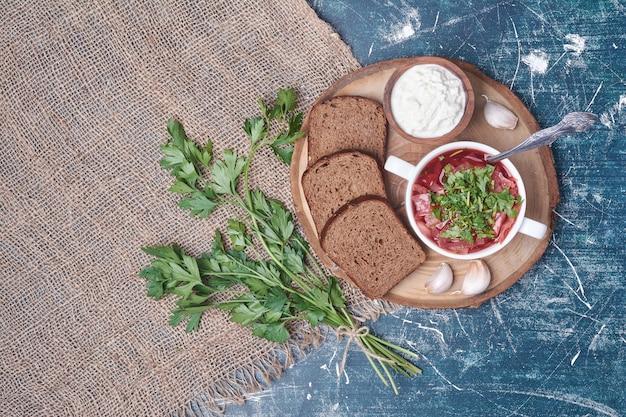Soupe aux légumes dans une tasse blanche avec du pain noir sur planche de bois.
