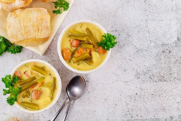 Soupe aux légumes frais et crémeux faits maison sur un bol blanc avec un petit pain et une cuillère.
