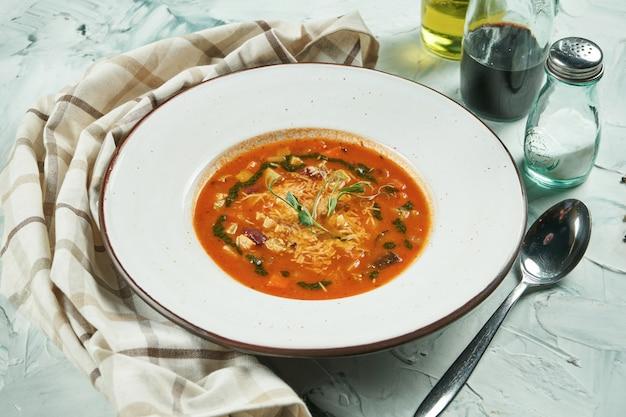 Soupe aux légumes ministrone italien classique à base de légumes de saison avec l'ajout de riz ou de pâtes dans un bol blanc sur fond blanc