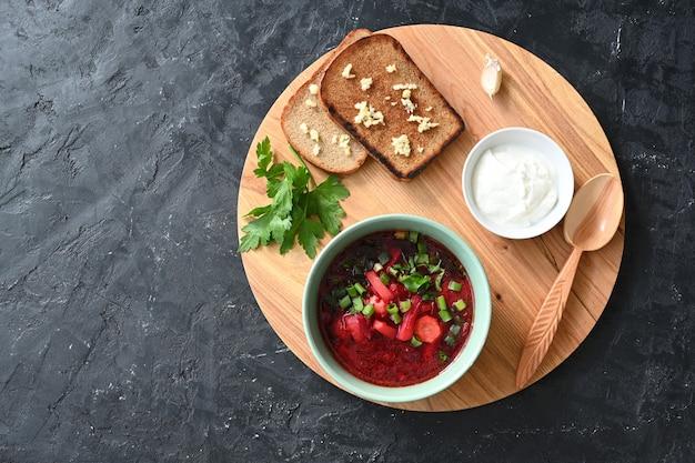 Soupe aux légumes russe traditionnelle ukrainienne, bortsch avec beignets à l'ail et pain.