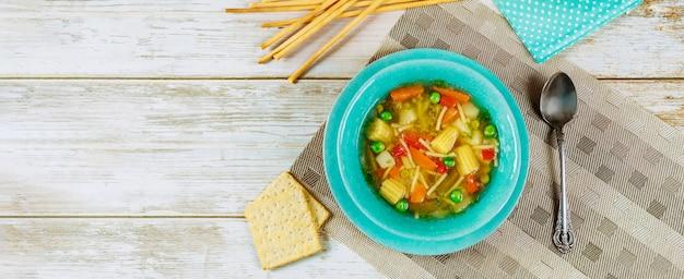 Soupe aux légumes saine avec des craquelins et des bâtonnets de pain.