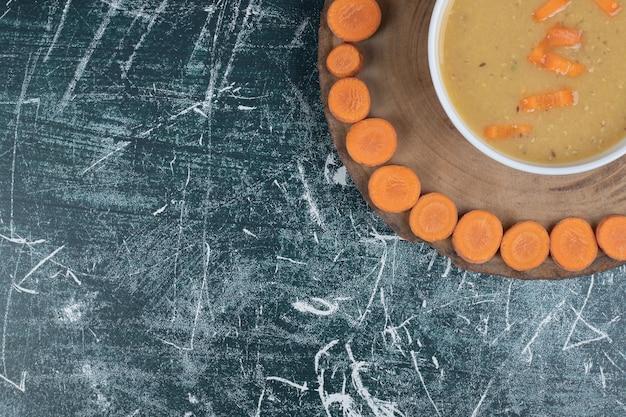 Soupe aux lentilles dans un bol blanc et des tranches de carottes.