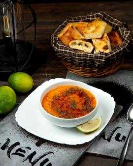 Soupe aux lentilles saupoudrée d'épices et d'une tranche de citron