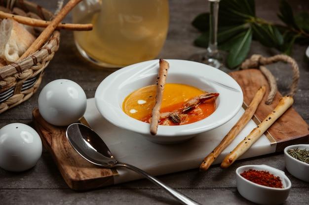 Soupe aux lentilles servie avec des bâtonnets de pain