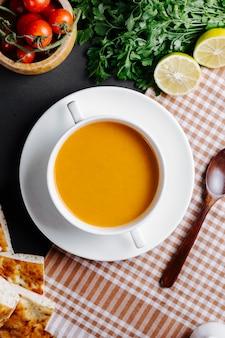 Soupe aux lentilles servie avec citron et légumes verts