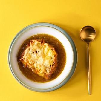 Soupe aux oignons français avec du fromage sur le mur rouge.