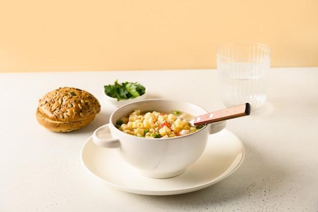 Soupe aux pâtes ditalini, pois, saucisse végétalienne sur table moderne.