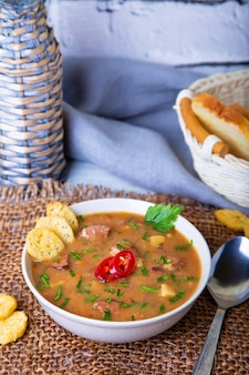 Soupe aux petits pois avec viande, saucisse fumée et croûtons.