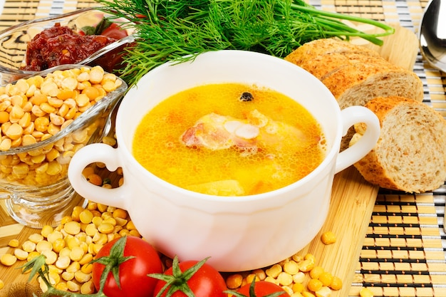 Soupe aux pois avec bacon. dans une tasse en céramique blanche. décoré avec de l'aneth et des tomates cerises.
