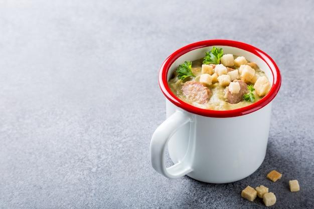 Soupe aux pois faite maison avec des saucisses et des croûtons