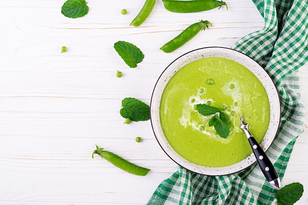 Soupe aux pois verts dans un bol sur la table en bois. cuisine française. vue de dessus