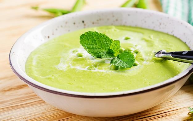 Soupe aux pois verts dans un bol sur la table en bois. cuisine française.