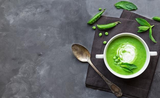 Soupe aux pois verts et à la menthe dans un bol sur fond de béton gris. vue de dessus avec espace pour le texte.