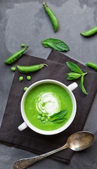 Soupe aux pois verts et à la menthe dans un bol sur fond de béton gris. vue de dessus.