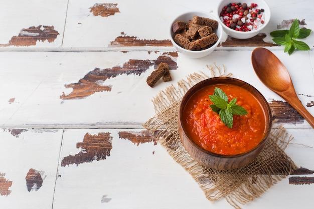 Soupe aux tomates dans un bol en bois avec des morceaux de pain grillé sur une table rustique