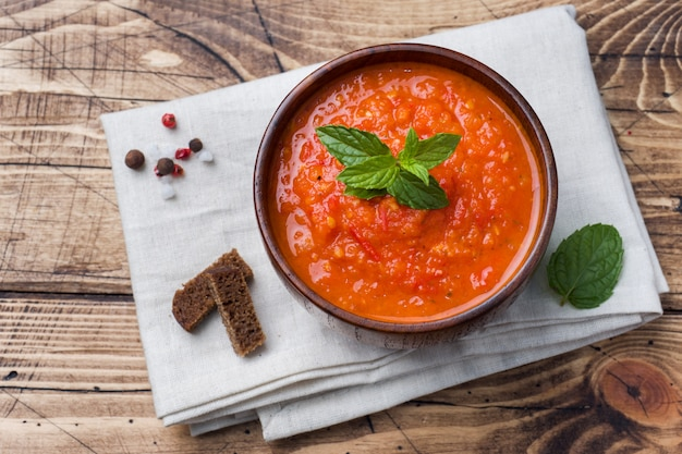 Soupe aux tomates dans un bol en bois avec des morceaux de pain grillé sur une table rustique.