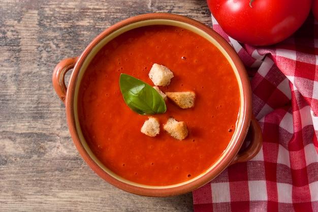 Soupe aux tomates dans un bol brun sur une table en bois. vue de dessus
