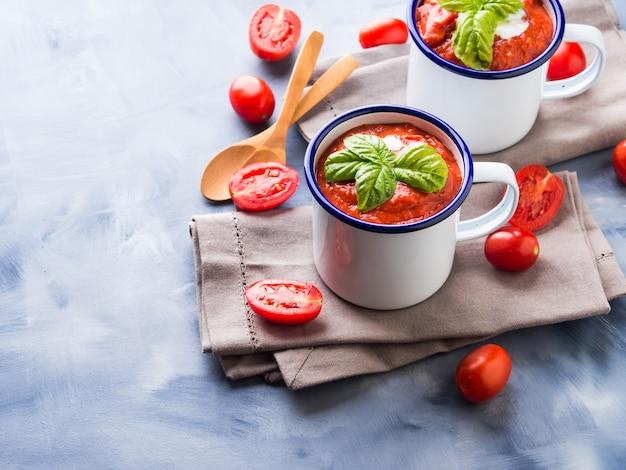 Soupe aux tomates dans des tasses en émail
