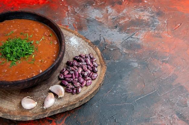 Soupe aux tomates haricots ail sur une planche à découper en bois sur la table des couleurs de mélange
