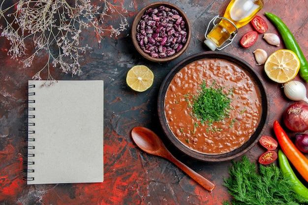Soupe aux tomates huile bouteille de haricots citron un bouquet de vert et cahier sur table de couleurs mixtes