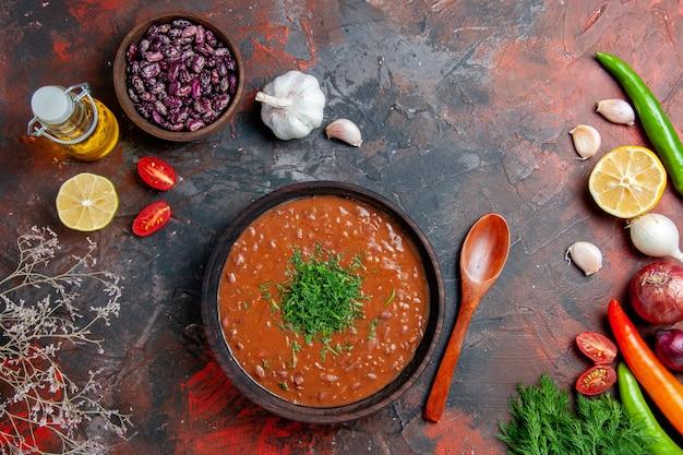 Soupe aux tomates huile bouteille de haricots citron et un bouquet de vert sur table de couleurs mixtes