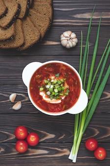 Soupe aux tomates maison avec du pain de seigle et de l'ail sur une table en bois sombre.