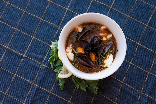 Soupe aux tomates avec moules, persil, basilic, philadelphie sur fond bleu foncé.