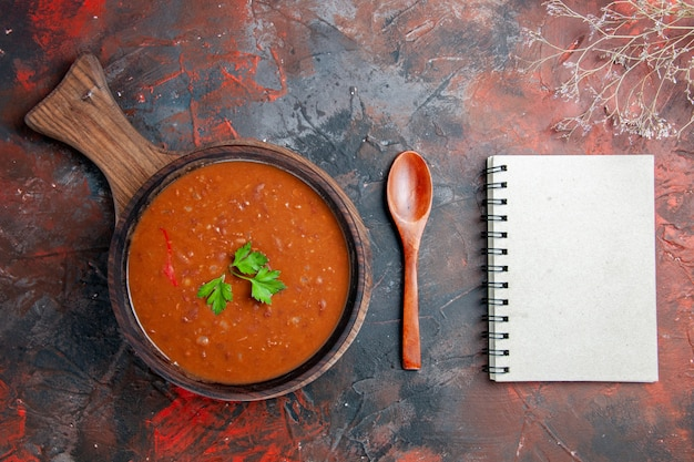 Soupe aux tomates sur une planche à découper brune et ordinateur portable sur une table de couleurs mélangées
