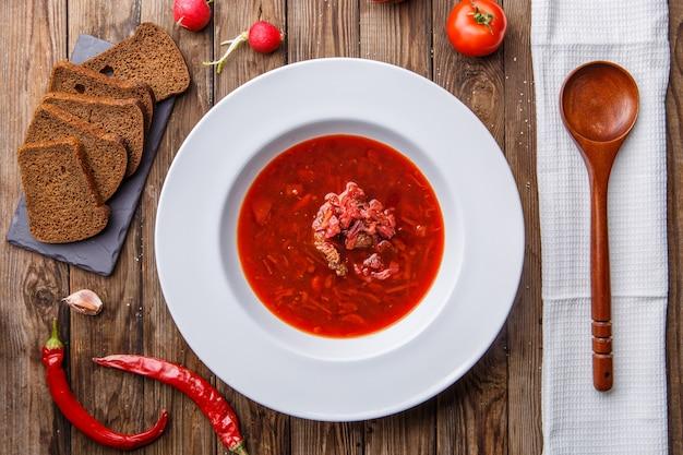 Soupe de betteraves dans une assiette blanche avec des légumes sur une table en bois. borch, cuisine traditionnelle russe
