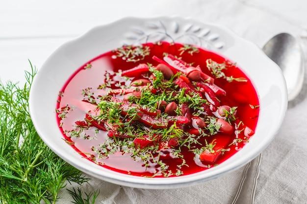 Soupe de betteraves végétarienne avec haricots et légumes dans une assiette blanche sur un fond en bois blanc.