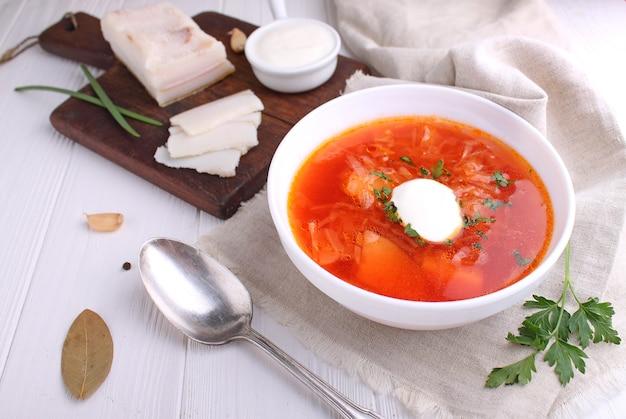 Soupe de bortsch rouge dans un bol blanc avec la crème sure et le persil, vue de dessus, sur fond blanc en bois.