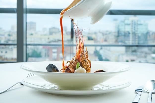 Une soupe de bouillabaisse rouge appétissante est versée dans un bol avec du saumon, des pétoncles, des langoustines et des moules, servie dans une assiette blanche sur une nappe blanche