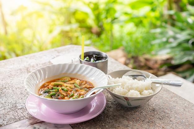 Soupe de boulettes de poisson aigre avec haricots longs et riz cuit sur la table, thai food