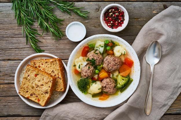 Soupe de boulettes de viande dans une assiette blanche sur une vieille table grise rustique en bois