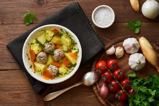 Soupe de boulettes de viande dans une assiette blanche sur une vieille table marron rustique en bois