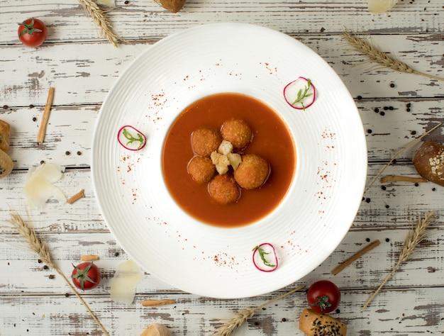 Soupe de boulettes de viande à la sauce tomate dans une assiette blanche.