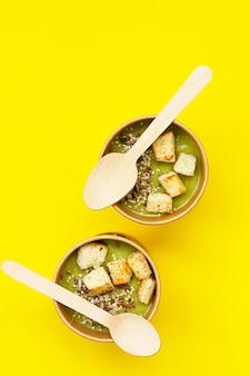 Soupe de brocoli frais avec croûtons et graines dans des contenants artisanaux