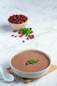 Soupe chaude aux haricots rouges dans un bol blanc place sur un sol en marbre blanc