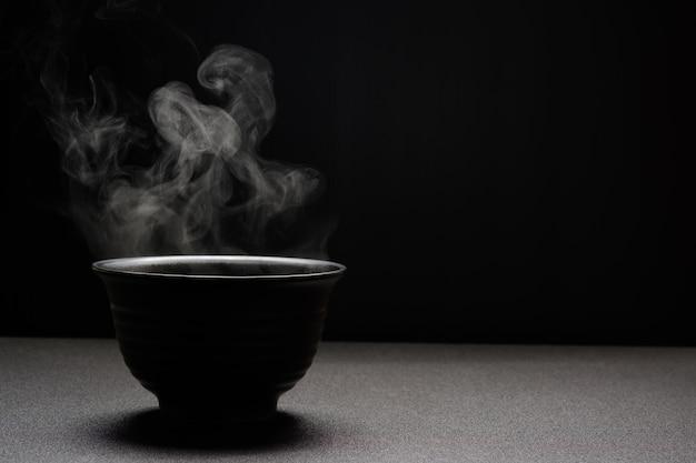 Soupe chaude dans un bol noir sur une table en bois, de la vapeur alimentaire et de l'espace de copie, mise au point sélective. concept d'aliments frais