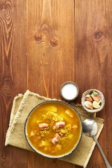 Soupe chaude d'hiver aux pois verts hachés, porc, bacon, fumé sur une table en bois brun foncé