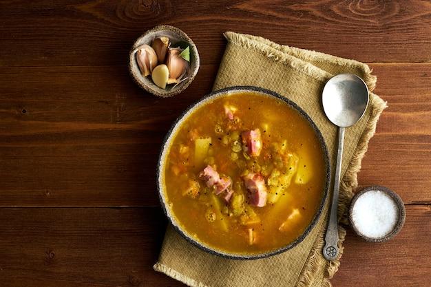 Soupe chaude d'hiver aux pois verts hachés, porc, bacon, fumée sur brun foncé