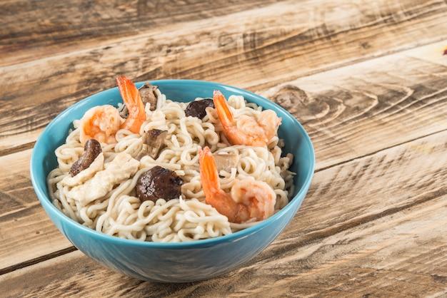 Soupe chinoise avec nouilles udon, porc, œufs durs, champignons et crevettes en gros plan dans un bol sur la table