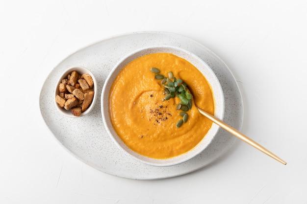 Soupe à la citrouille d'automne servi des craquelins et microgreens isolés sur tableau blanc
